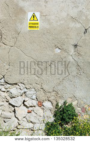 Warning yellow triangle with an exclamation point. On an old wall crumbling. The cracks indicate that is about to fall.