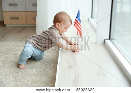 Cute baby boy and American flag on wooden windowsill
