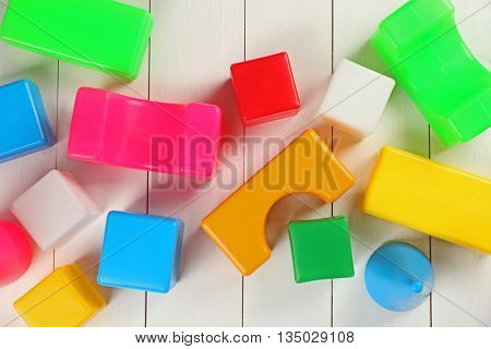 Colorful  children's building blocks on white wooden background