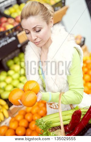 Woman at the market.She is buying fresh fruits and vegetables at a market.