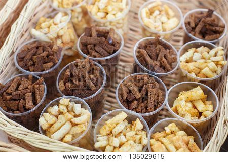 Croutons snack in plastic cups for party. Croutons crackers of white and brown whole grain bread.