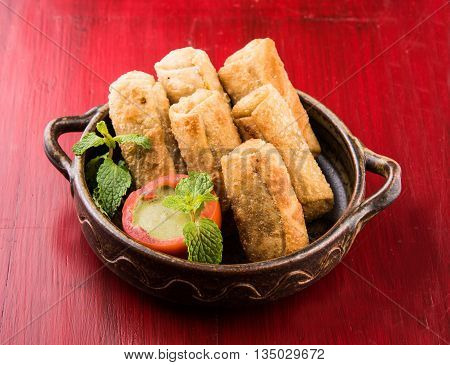 veg roll in brown ceramic bowl with mint leaf