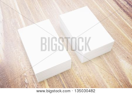 Two stacks of blank business cards on wooden surface. Mock up 3D Rendering