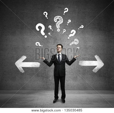 Different direction concept with confused businessman question mark and arrow sketches on concrete background