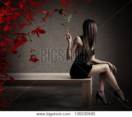 Woman sitting on a table with a red rose