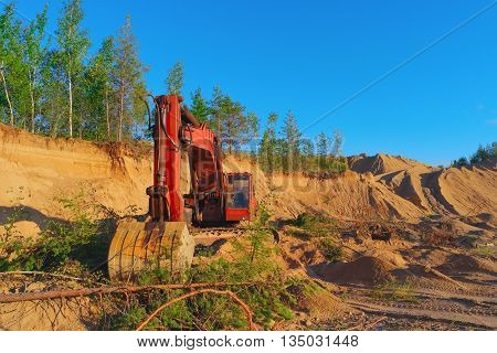 Excavator working on sand dunes in quarry