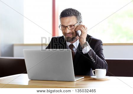 Businessman with laptop and cellphone in cafe