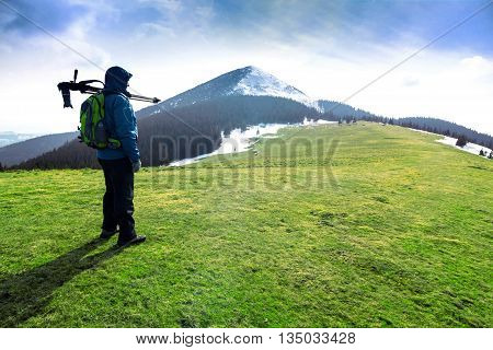 Lonely photographer hiking in mountains in sunny day