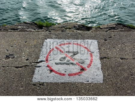 No Swimming Sign Painted on Crumbling Sidewalk along a public lake way