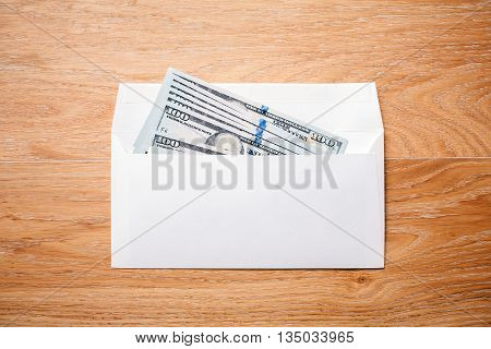 Top view of blank envelope with dollar banknote on wooden desktop. Mock up