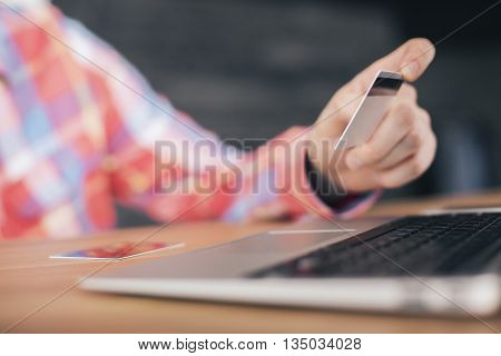 Online shopping concept with blurry man hand holding credit card over laptop keyboard