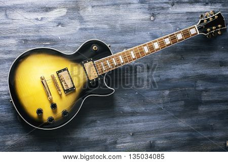 Top view of black and yellow electric guitar on dark wooden surface