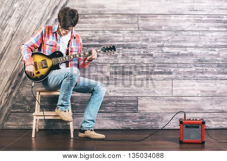 Young man sitting on chair in studio with wooden floor and wall playing electric sunburst guitar connected to amplifier