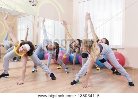 Group of Five Professional Sportswomen Making Stretching Exercises with Trunk Bending in Sport Class. Horizontal Shot