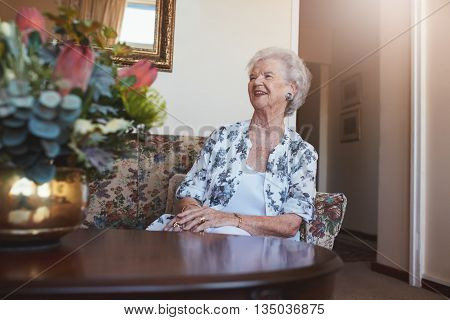 Portrait of a senior woman sitting on a sofa at old age home looking away and smiling.