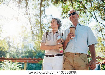 Senior Tourists Walking Through A Park