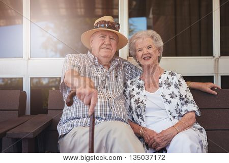 Elderly Couple Sitting Relaxed On A Bench Outdoors