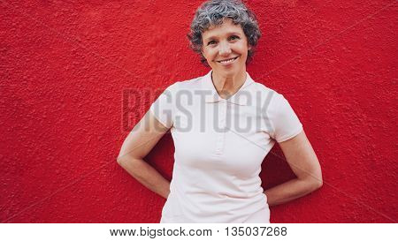 Portrait of happy middle aged woman standing relaxed against red background. Cheerful mature woman leaning to a red wall.