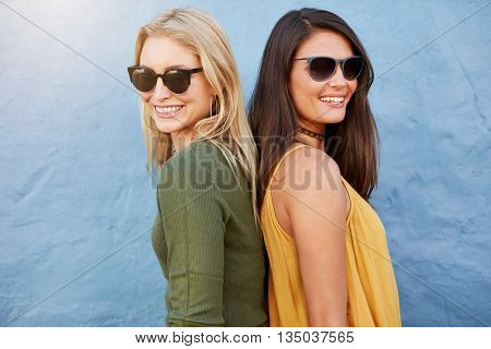 Two Women Smiling Back To Back