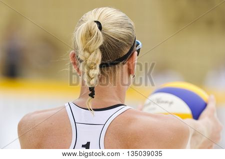 Volleyball player is a female athlete volley ball player getting ready to serve the ball.