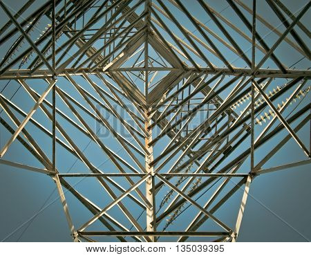Metalic power line tower structure against blue sky