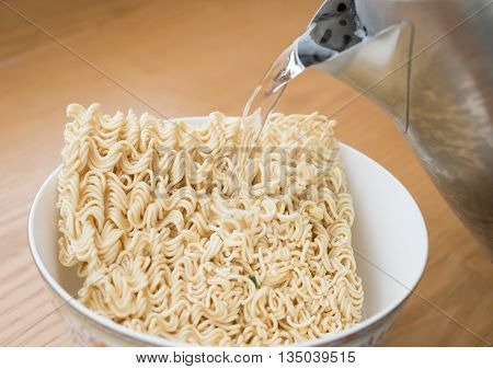 pouring hot water to prepare instant noodles