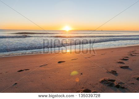 Sunrise over footprints on beach Papamoa Tauranga New Zealand