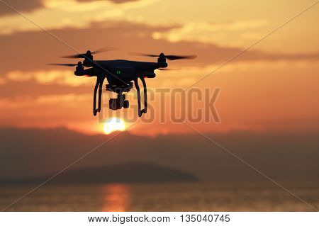 KAGAWA, JAPAN - JUNE 19, 2016: Remote controlled drone Dji Phantom 3 equipped with high resolution video camera flying above the sea against a sunset sky.