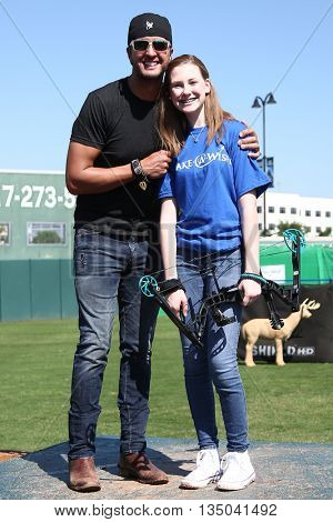 ARLINGTON, TX - APR 18: Recording artist Luke Bryan (L) poses with a Make A Wish member at the ACM & Cabela's Great Outdoor Archery Event at the Texas Rangers Youth Ballpark on April 18, 2015.