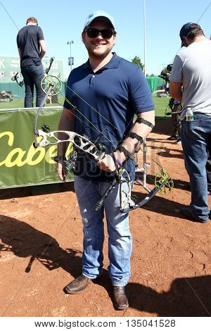 ARLINGTON, TX - APR 18: Recording artist Josh Abbott poses with a bow at the ACM & Cabela's Great Outdoor Archery Event at the Texas Rangers Youth Ballpark on April 18, 2015.