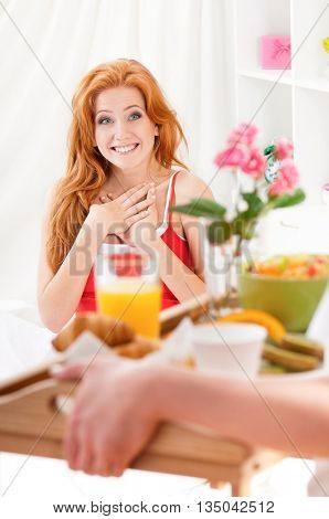Happy relaxed woman in bed with breakfast early. Sweet croissants and orange juice for breakfast in bed.