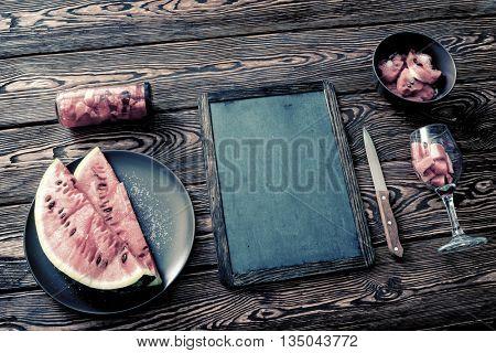 Mockup of a chalkboard on dark desktop with sliced watermelon. Top view.