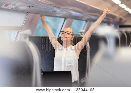 Businesswoman traveling by train, streching her upper body arms reised taking a break from laptop work. Business travel concept.