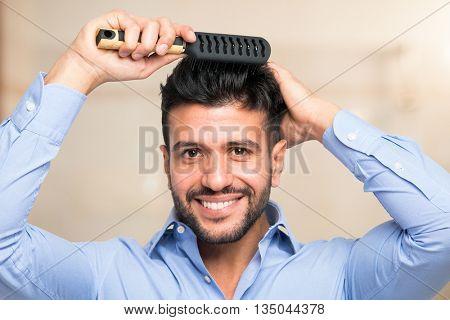 Happy man combing his hair