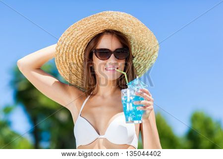 Woman relaxing at the pool with cocktail
