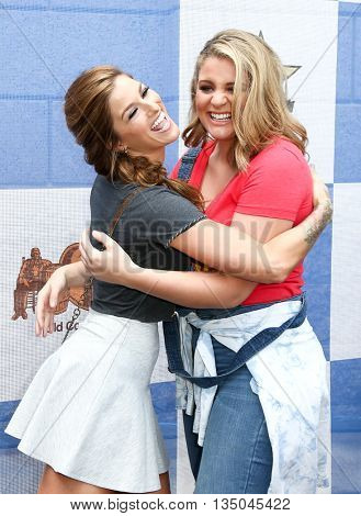 ARLINGTON, TX - APR 18:Cassadee Pope (L) and Lauren Alaina attend the Cracker Barrel Old Country Store Country Checkers Challenge at Globe Life Park in Arlington on April 18, 2015 in Arlington, Texas.