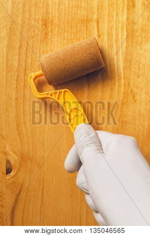 Hand with paint roller applying acrylic lacquer on wooden board non toxic water based lacquer wood coating for furniture redecorating.