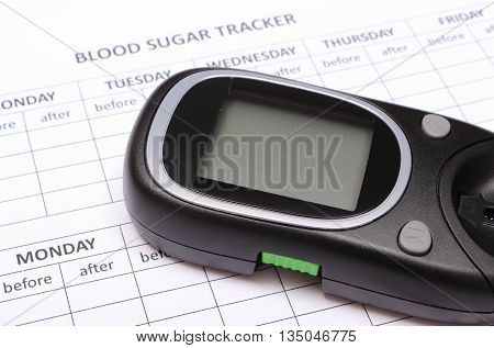 Glucose meter lying on empty medical forms for measurement sugar in blood concept for healthy lifestyle and diabetes