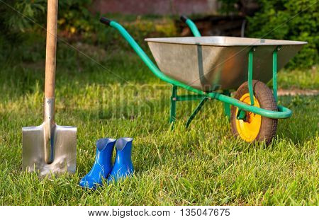 Blue rubber boots on a background of green lawn. Bright inventory gardener. Trolley and shovel for the garden care.