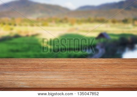 Tabletop wooden with green rice field blurred background, stock photo