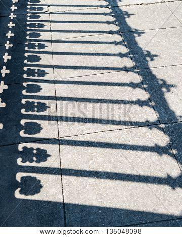 Shadows of a cast iron fence on a concrete sidewalk