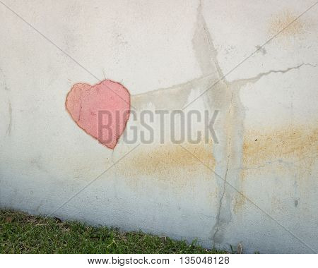 Plaster wall with cracks and an added heart.