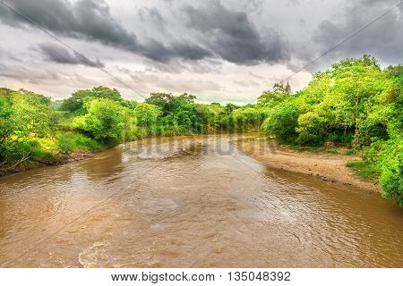 Watercourse On Brown River In Green Nature