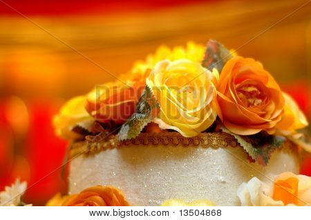 Wedding cake with yellow and orange rose on top. Shallow depth of field with a very blurry background