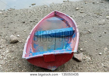 old boat filled with water on the banks of a dried lake