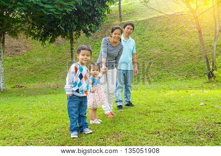 Outdoor portrait of happy asian family at park