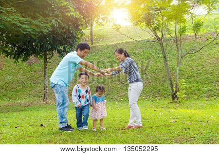 Asian family outdoor quality time enjoyment asian people playing during beautiful sunset.