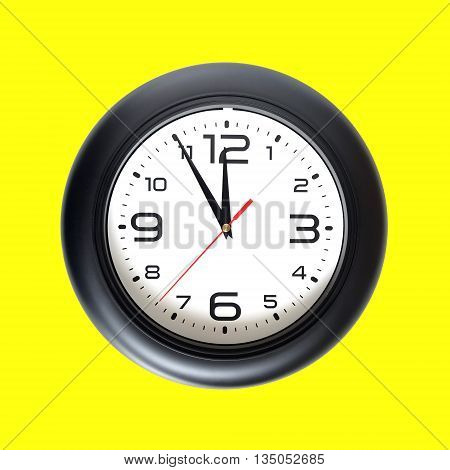Big round wall clock, with a black rim isolated on yellow background close-up and arrows showing almost twelve o'clock