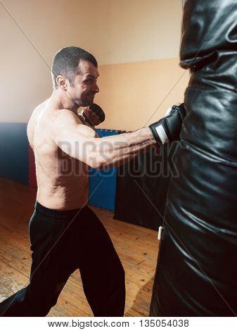 Half-naked strong man boxing punching bag in sport gym. Man training with punching bag.