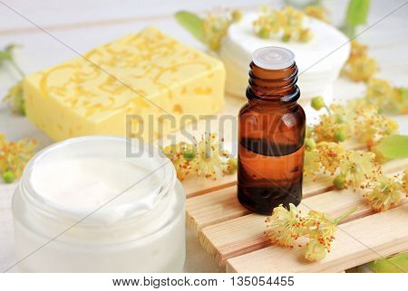 Herbal cosmetic products. Tilia (lime blossom) ethereal oil bottle, fresh facial cream, yellow soap bar.